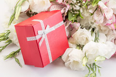 Gift on bouquet of flowers Stock Photos