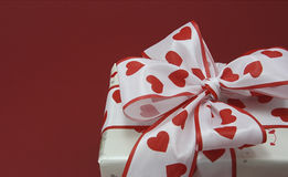 Gift with a bow. On red background Royalty Free Stock Image