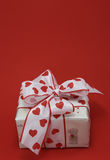 Gift with a bow. On a red background Royalty Free Stock Photos