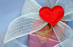 Gift with a bow and a heart. On blue organza to Valentine's Day Royalty Free Stock Photography