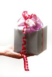 A gift with a bow is held Stock Image