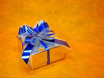 Gift box. Silver gift box with blue ribbon royalty free stock images