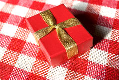 Gift box. In red with yellow ribbons on a red and white background royalty free stock photography