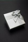 Gift Box. With Silver Ribbon against Black background Royalty Free Stock Photo