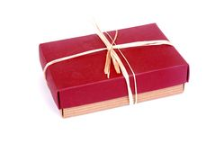 Gift box. A closed beige cardboard gift box with dark red lid and beige ribbon. Image isolated on white studio background Royalty Free Stock Photography