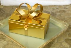 Gift box. Gold gift box with a bow on a tray Stock Photography