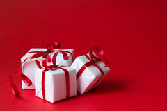 Gift box. White gift box with red ribbon isolated on red color background Stock Images