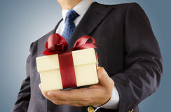Gift box. Businessman holds out the gift box , background Royalty Free Stock Image