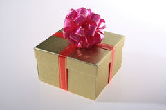Gift box. Gold color gift box with pink color ribbon Royalty Free Stock Photo