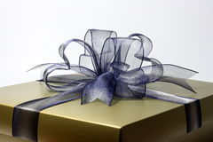 Gift box. A gold gift box with blue ribbon over white background Stock Photos