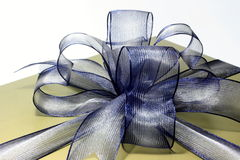 Gift box. A gold gift box with blue ribbon over white background Stock Images