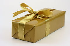 Gift Box. A gold gift box with gold ribbon over white background Royalty Free Stock Photo