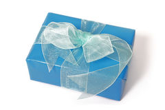 Gift box. Present beautifully wrapped in blue paper tied with metallic colored ribbon royalty free stock photography