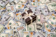 Gift box above dollars bills. As background Stock Images