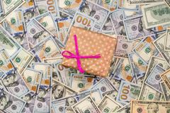 Gift box above dollars bills. As background Stock Photo