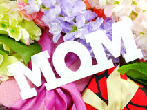 Gift box and artificial flowers for mother's day. Close up of text mom word copy with gift and fllower stock photo