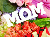 Gift box and artificial flowers for mother's day. Close up of text mom word copy with gift and fllower stock image