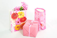 Gift box and bags. Pink gift box and floral paper bags with flowers on white background Royalty Free Stock Image