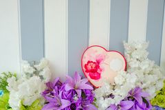 a gift box on a bed of flowers stock images