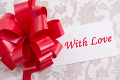Gift box with big bow and greeting card with text Stock Photos