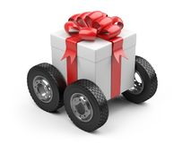 Gift box on a big tires wheels. Royalty Free Stock Images