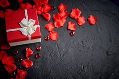Gift box on black stone table. Romantic holiday background with rose petals. Gift box on black stone table. Sweet romantic holiday background with rose petals stock images