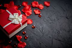 Gift box on black stone table. Romantic holiday background with rose petals. Gift box on black stone table. Sweet romantic holiday background with rose petals royalty free stock photos