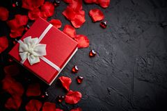 Gift box on black stone table. Romantic holiday background with rose petals. Gift box on black stone table. Sweet romantic holiday background with rose petals stock photos