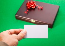 Gift box with blank card. Gift box and blank card in hand Royalty Free Stock Images
