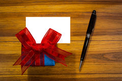 Gift box with blank card and pen on wooden table. Royalty Free Stock Photography