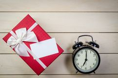 Gift box with blank name card and alarm clock. On wooden board background Stock Images