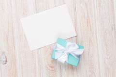 Gift box and blank photo frame or greeting card. On white wooden table. Top view Royalty Free Stock Images