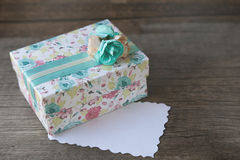 Gift box with blank tag on wood background Royalty Free Stock Photos