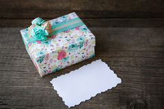 Gift box with blank tag on wood background Royalty Free Stock Photo