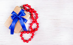 Gift box with blue bow and red coral beads on a white wooden background. Surprise to the woman. Stock Photo