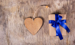 Gift box with blue bow and Valentine. Surprise on Valentine`s Day. Wooden heart. Copy space. Valentine`s day. Royalty Free Stock Photo