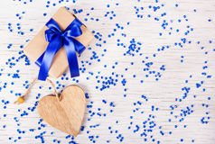 Gift box with blue bow and valentines on a white background with sparkles. Valentine`s Day. Copy space. Royalty Free Stock Image