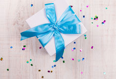 Gift box with blue bow on wood table Royalty Free Stock Images