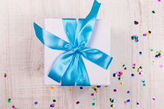 Gift box with blue bow on wood table Royalty Free Stock Image