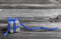 Gift box with blue checked ribbon on wooden grey background.