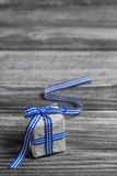 Gift box with blue checked ribbon on wooden grey background. Royalty Free Stock Images