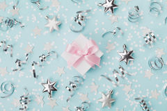 Gift box on blue christmas background decorated confetti and silver stars top view. Flat lay. Gift box on blue christmas background decorated confetti and Royalty Free Stock Photography