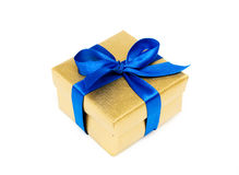 Gift box with a blue ribbon. Golden gift box with a blue ribbon on a white background Royalty Free Stock Photography