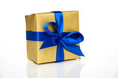 Gift box with a blue ribbon. Golden gift box with a blue ribbon on a white background with reflection Stock Photo