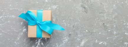 Gift box with blue ribbon on gray background. Top view banner with copy space for you design. holidays concept royalty free stock photos
