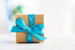Gift box with blue ribbon. In white wall room stock photography