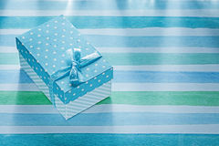 Gift box on blue striped tablecloth holidays concept Stock Image