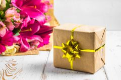 Gift in a box and a bouquet of flowers on a white wooden table. Birthday party. Gift in a box and a bouquet of flowers on a white wooden table. Birthday party Stock Images