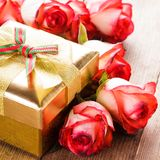 Gift box and bouquet of roses Stock Photos