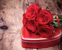 Gift box and bouquet of roses on wooden background Stock Photo
